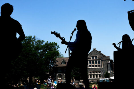 shadowed students play in a band on a stage on the Quad