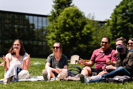 students sit on the Quad and listen to the bands