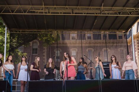 a group of singers perform on stage on the Quad