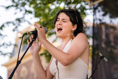 student sings into a mic on a stage on the Quad