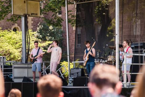 students sing and play guitar in band on a stage on the Quad