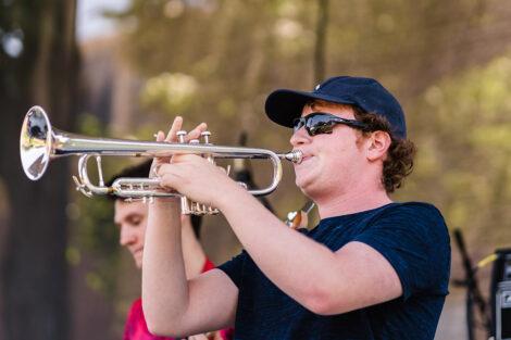 student plays trumpet on stage on Quad