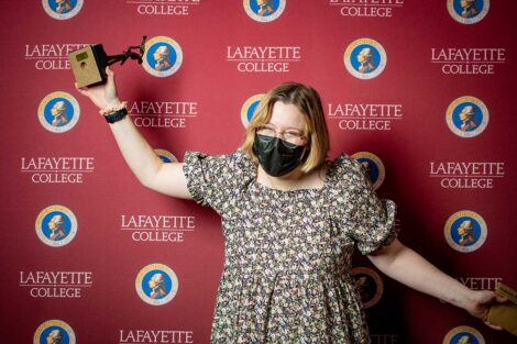 Caitlyn Dempsey '22 holding Aaron O. Hoff Award statue and standing in front of Lafayette College backdrop