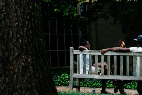 student and family members of 2021 sit on a bench near Colton Chapel