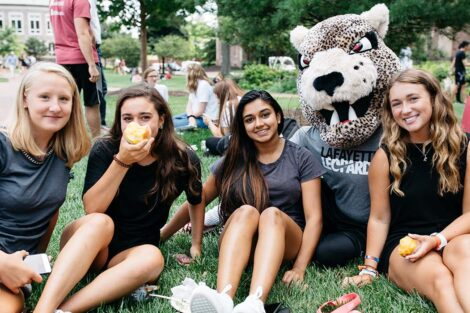 Smiling students on the Quad with the Leopard