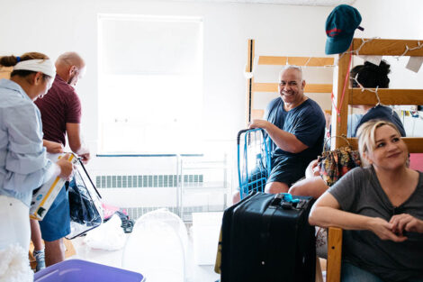 parents unpack in a dorm room and smile