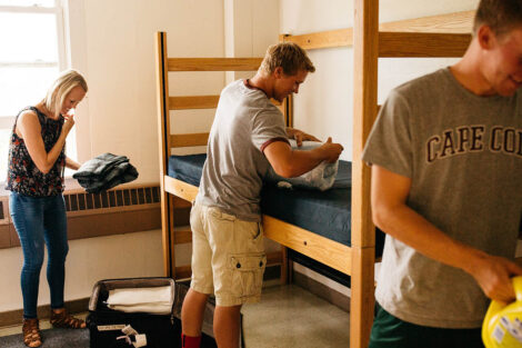 students and parent unpack in a dorm room