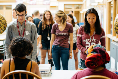 students stand at a sign-in table in Farinon
