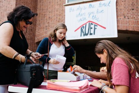 a student and parent at a sign-in table near Ruef