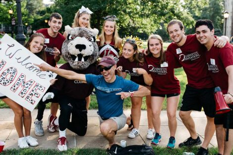 a group of students and the leopard cheer with a dad