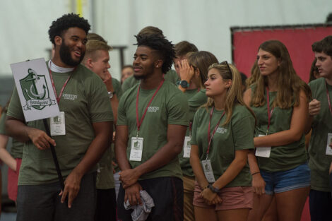students in ogreen shirts smile and talk inside Kirby Sports Center