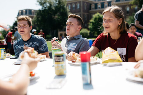 students eat together at a table on the Quad
