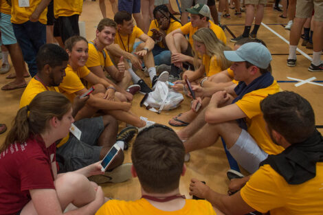 Class of 2021 students in yellow shirts sit together on the gym floor of Kirby Sports Center