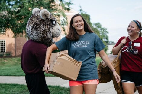 students carry boxes and smile on move-in day