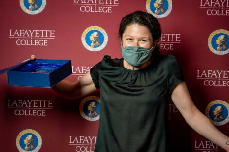 Dana Cuomo holding Aaron O. Hoff Award and standing in front of Lafayette College backdrop