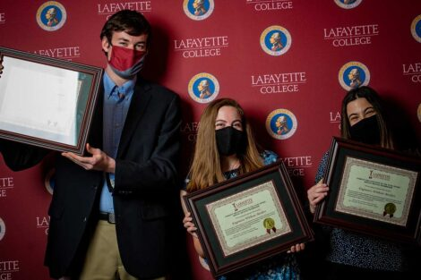 Student representatives of Engineers Without Borders holding Aaron O. Hoff Awards and standing in front of Lafayette College backdrop