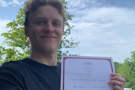 Erik Mathews holds certificate