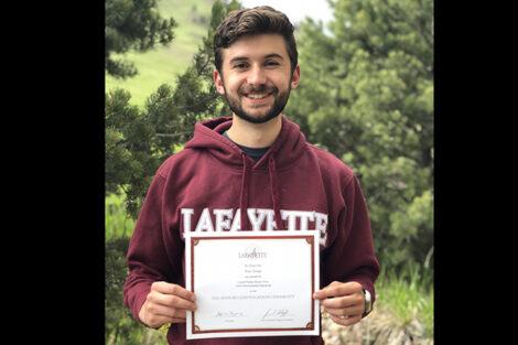 Evan Savage holds certificate