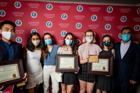 Student representatives of International Students Association holding Aaron O. Hoff Awards and standing in front of Lafayette College backdrop