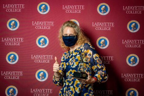 Janine Block '94 holding Aaron O. Hoff Award and standing in front of Lafayette College backdrop