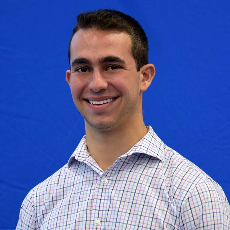 Josh Ingber smiles in button down shirt in front of a blue backdrop