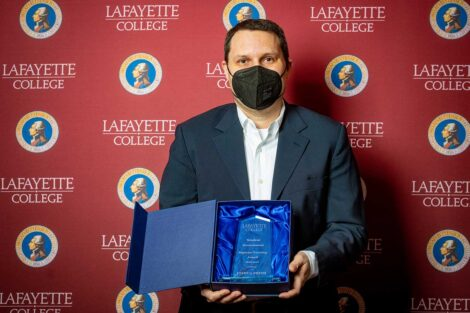 Joshua Smith holding Aaron O. Hoff Award and standing in front of Lafayette College backdrop