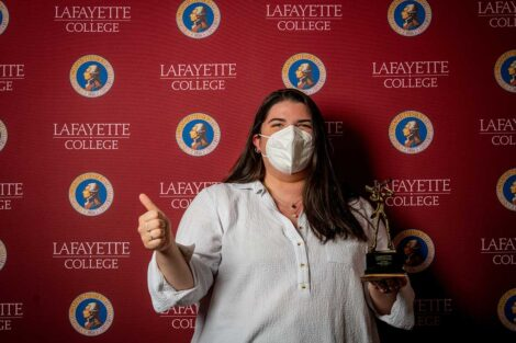 Kelsey Moum '21 holding Aaron O. Hoff Award statue and standing in front of Lafayette College backdrop