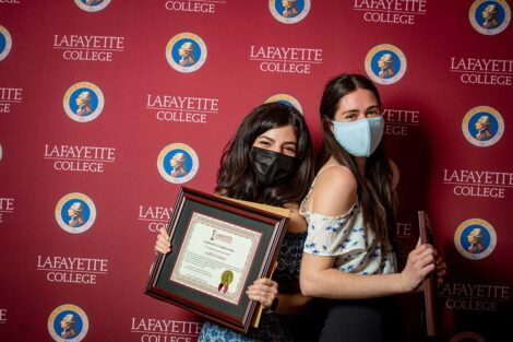Student representatives of LafKid Connect holding Aaron O. Hoff Awards and standing in front of Lafayette College backdrop