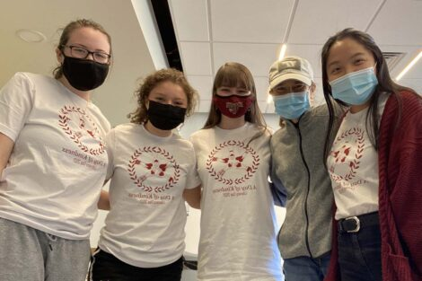 Five masked students stand next to each other all wearing Literacy Day shirts