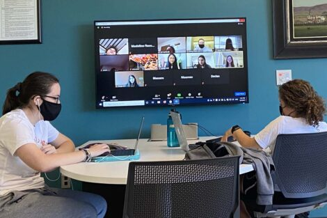 Two students sit at a table. A wall-mounted TV displays their laptop screens and shows a group of participants on Zoom for Literacy Day