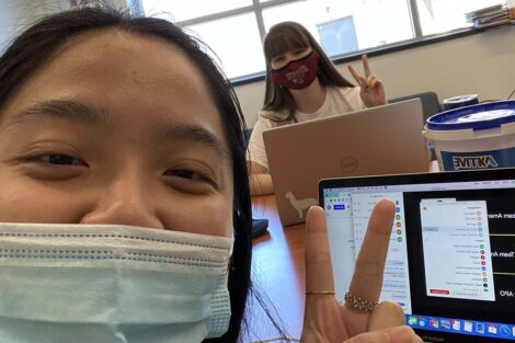 Two students at laptops flash the peace sign