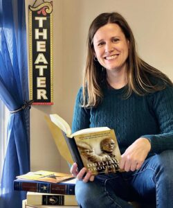 Mary Jo Lodge holds Dueling Grounds book, theatre sign in background