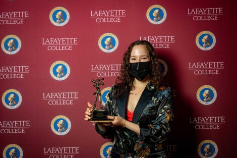 Milena Berestko '22 holding Aaron O. Hoff Award statue and standing in front of Lafayette College backdrop