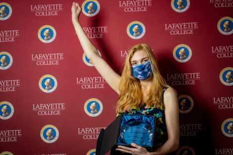 Morgan Limmer '21 holding Aaron O. Hoff Award statue and standing in front of Lafayette College backdrop