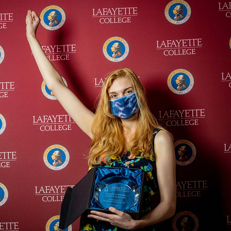Morgan Limmer celebrates her Hoff Award. She raises her arm in victory while holding an award. She wears a dress and mask.