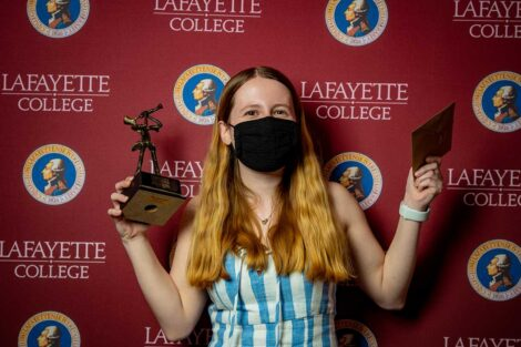 Nicole Segalini '21 holding Aaron O. Hoff Award statue and standing in front of Lafayette College backdrop