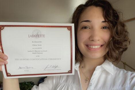 Olivia Scott holds certificate