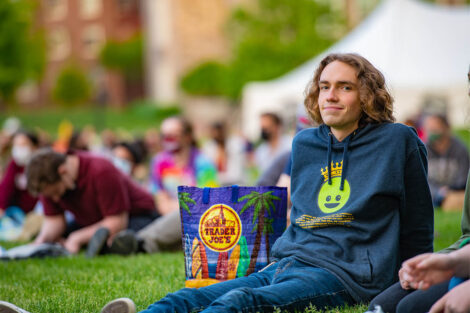 A student smiles while sitting on the Quad.