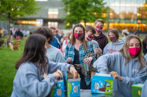 Students, wearing masks, grab a pint of ice cream.