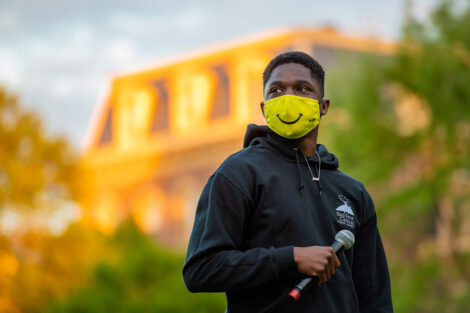 A student, wearing a yellow smiley face mask, holds a microphone in front of Pardee Hall.
