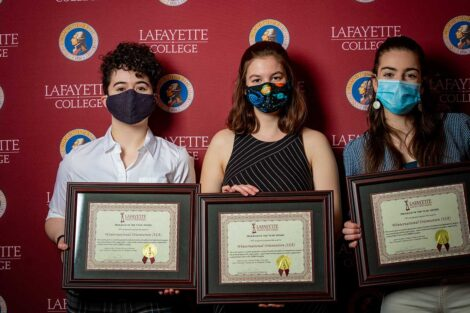 Student representatives of Winternational Orientation holding Aaron O. Hoff Awards and standing in front of Lafayette College backdrop