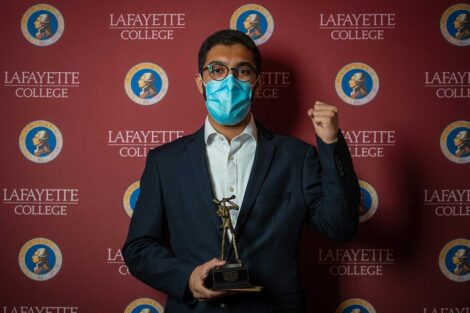 Yazdan Basir '23 holding Aaron O. Hoff Award statue and standing in front of Lafayette College backdrop