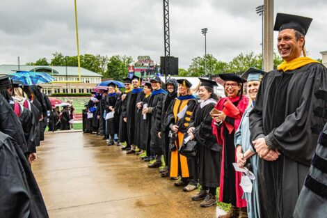 faculty smile as seniors walk toward Fisher Field Commencement 2021 3