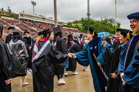 faculty smile as seniors walk toward Fisher Field Commencement 2021 4