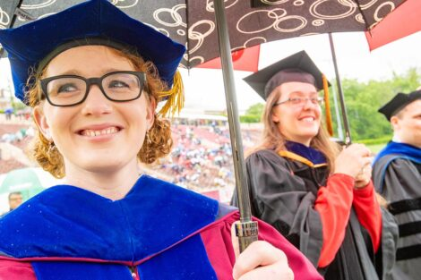 faculty smile as seniors walk toward Fisher Field Commencement 2021