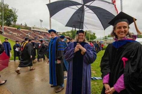 faculty smile as seniors walk toward Fisher Field Commencement 2021 6