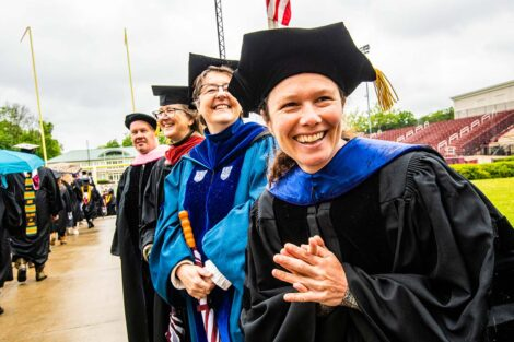 faculty smile as seniors walk toward Fisher Field Commencement 2021 7