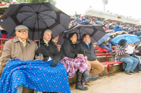 family members sit in stands with umbrellas Commencement 2021