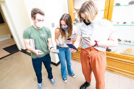 students in masks look at Van Wickle geology rock walll