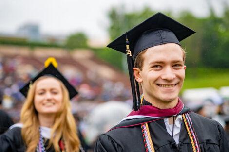 senior in cap and gown smiles Commencemen 2021